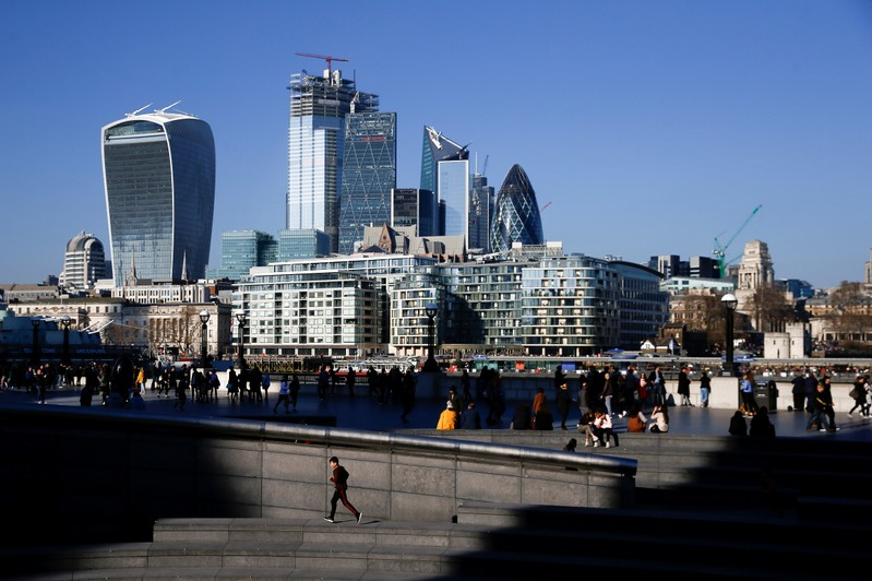 FILE PHOTO: The financial district can be seen as a person runs in the sunshine on London's south bank