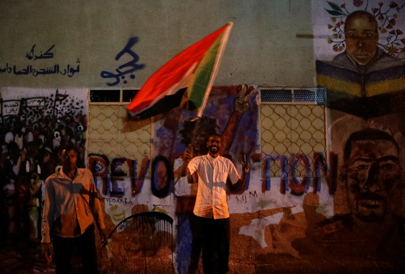A Sudanese protester waves a national flag as he arrives a mass protest in front of the Defence Ministry in Khartoum