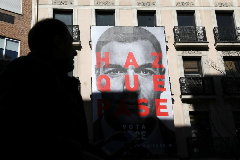 A man walks past an electoral poster of Spain's Socialist (PSOE) leader and current PM Sanchez outside the PSOE headquarters in Madrid