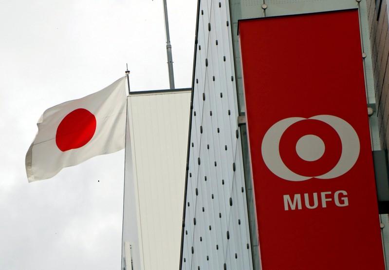 Japan's national flag is seen behind the logo of Mitsubishi UFJ Financial Group Inc (MUFG) at its bank branch in Tokyo