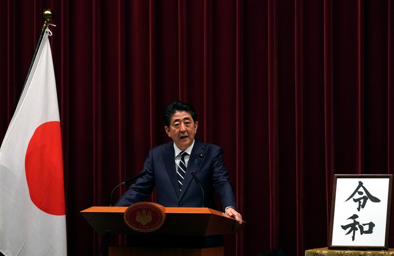 FILE PHOTO: Japan's Prime Minister Shinzo Abe delivers a press conference standing next to the calligraphy 'Reiwa' which was chosen as the new era name at the prime minister's office in Tokyo