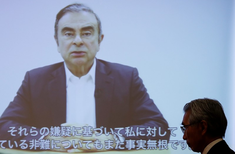 FILE PHOTO: Junichiro Hironaka, chief lawyer of the former Nissan Motor chairman Carlos Ghosn, walks in front of a screen showing Ghosn's video statement during a news conference at Foreign Correspondents' Club of Japan in Tokyo
