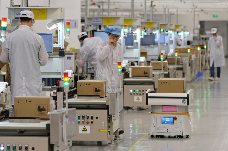 FILE PHOTO: Employees work on a mobile phone production line at Huawei's factory campus in Dongguan, Guangdong province