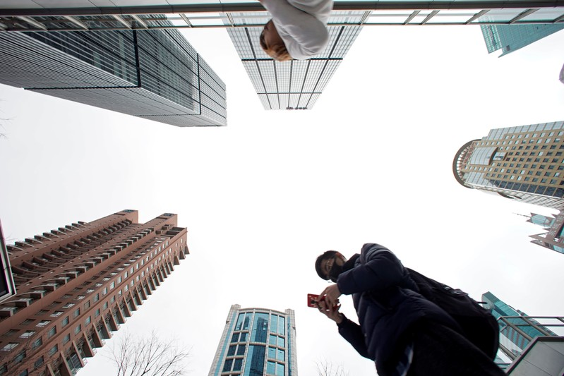 FILE PHOTO:  A man checks phone at Lujiazui financial district in Pudong