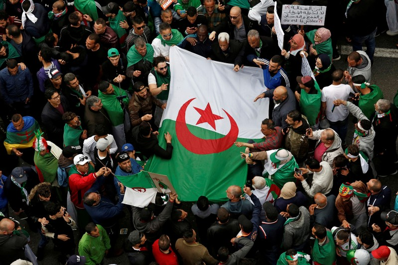 FILE PHOTO: Demonstrators hold flags and banners as they return to the streets to press demands for wholesale democratic change well beyond former president Abdelaziz Bouteflika's resignation in Algiers
