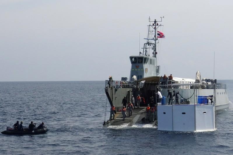 A Royal Thai navy ship drags a floating home, lived in by an American man and his Thai partner, in the Andaman Sea, off Phuket Island in Thailand
