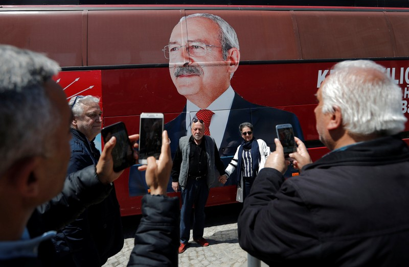 Supporters of the main opposition CHP pose in front of a party bus with a picture of their leader Kemal Kilicdaroglu on it, in Istanbul