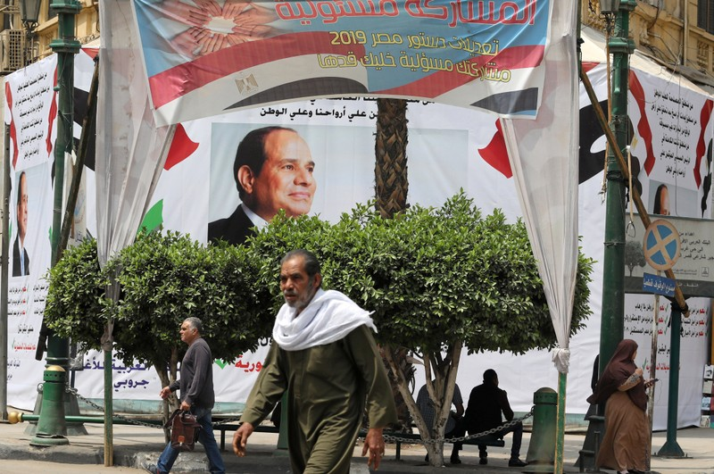 Pedestrians walk in front of a banner of the Egyptian President Abdel Fattah al-Sisi before the upcoming referendum on constitutional amendments in Cairo