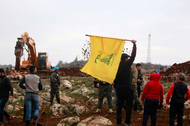 A man holds a Hezbollah flag at Meis al-Jabal village