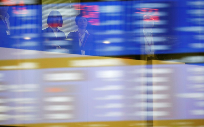 Visitors are seen as market prices are reflected in a glass window at the TSE in Tokyo