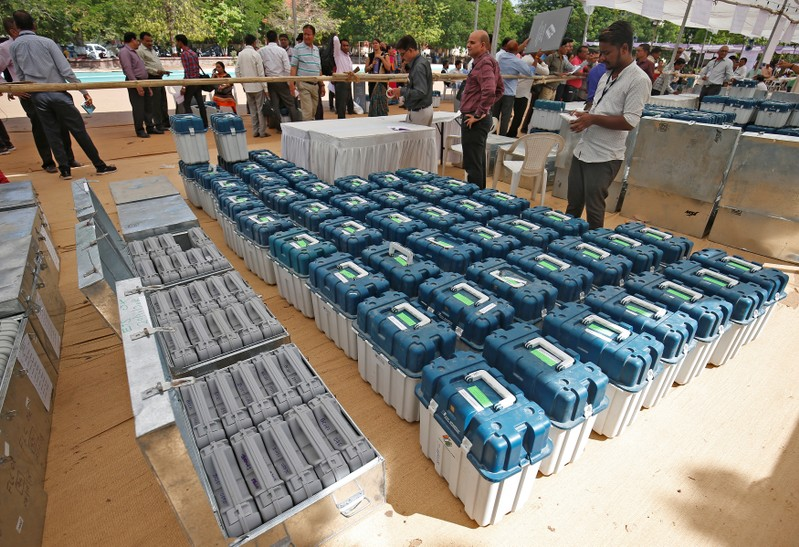 Polling officers wait to collect the election materials at a distribution centre ahead of third phase of general elections in Ahmedabad