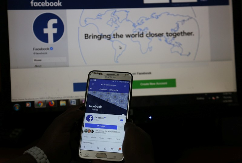 An illustration photo shows the Facebook page displayed on a mobile phone internet browser held in front of a computer screen at a cyber-cafe in downtown Nairobi