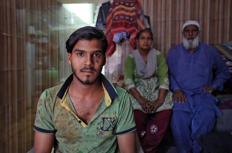 Mohammad Rafiq poses with his parents inside their house in Ahmedabad