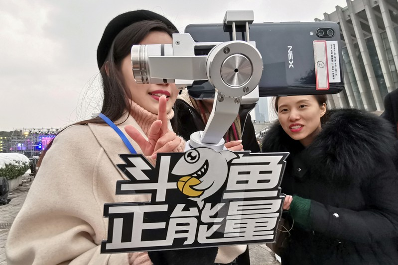 FILE PHOTO: A girl broadcasts live from a phone as she holds a selfie stick with a sign of the live-streaming platform DouYu during an event celebrating the new year in Wuhan