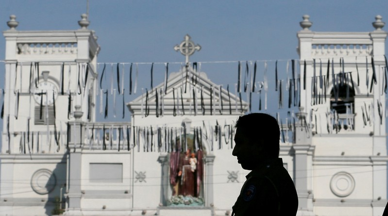 A security personnel observes three minutes of silence as a tribute to victims, two days after a string of suicide bomb attacks on churches and luxury hotels across the island on Easter Sunday, near St Anthony Shrine in Colombo