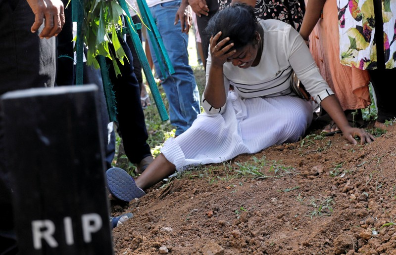 A woman reacts during a mass burial of victims, two days after a string of suicide bomb attacks on churches and luxury hotels across the island on Easter Sunday, in Colombo