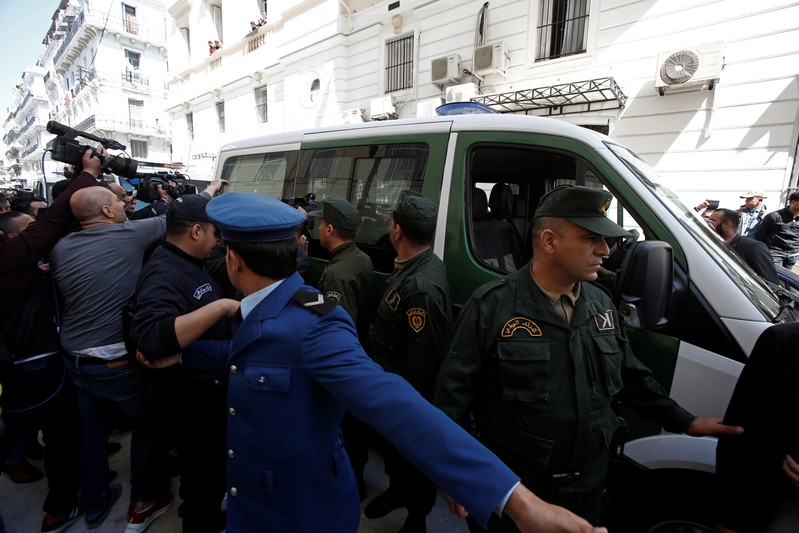 Media and police surround a convoy of police vehicles as businessmen suspected of corruption are driven to court in Algiers