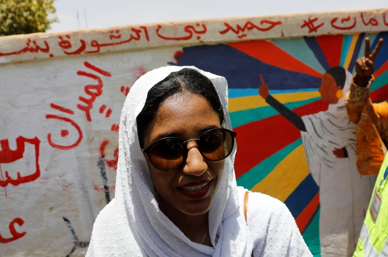 FILE PHOTO: Alaa Salah, a Sudanese protester whose video gone viral and make her an icon for the mass anti-government protests, stands in front of a mural depicting her in front of the Defence Ministry in Khartoum
