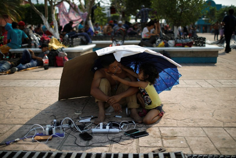 A migrant from Honduras watch other migrants' cellphones as they gather in an improvised shelter during a break in their journey towards the United States, in Escuintla