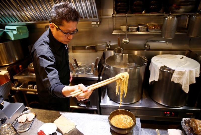 Kenji Saito cooks at his ramen noodle shop in Tokyo