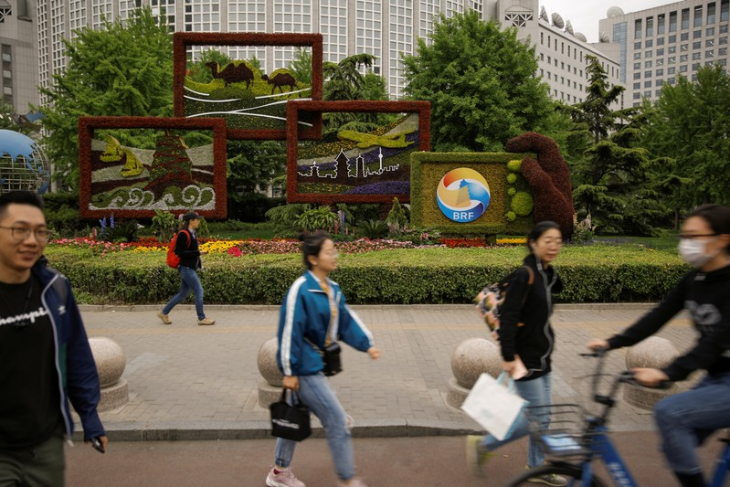 FILE PHOTO: People walk past a flower arrangement set up to mark the upcoming Belt and Road Forum in Beijing