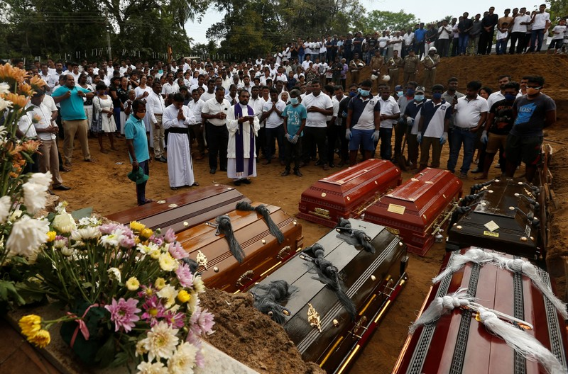 People participate in a mass funeral in Negombo