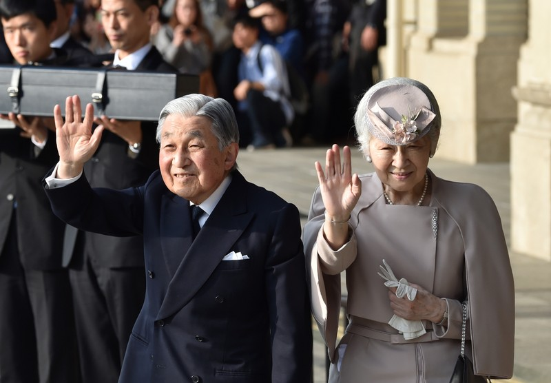 FILE PHOTO: Japan's Emperor Akihito, accompanied by Empress Michiko, waves to well-wishers before leaving Ujiyamada Station after their visit to Ise Jingu shrine in Ise, Japan