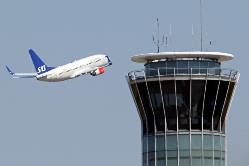FILE PHOTO: A Scandinavian SAS airline passenger plane flies near the air traffic control tower at Roissy airport, near Paris
