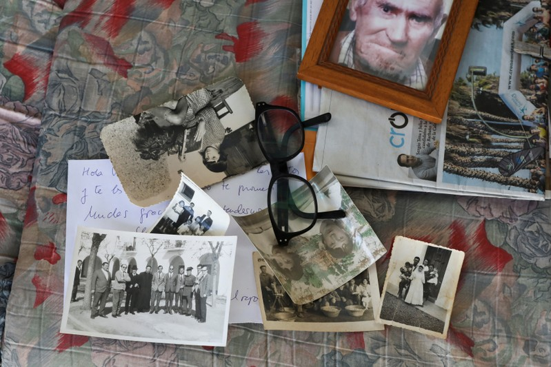 Old pictures belonging to Vicenta Prado's family lie on a couch after an interview with Reuters in Guadiana del Caudillo