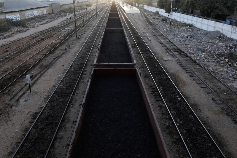 A cargo train loaded with coal dust, moves past the port area near City Station in Karachi