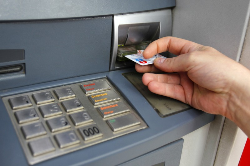 FILE PHOTO - Man uses traditional ATM in Bucharest