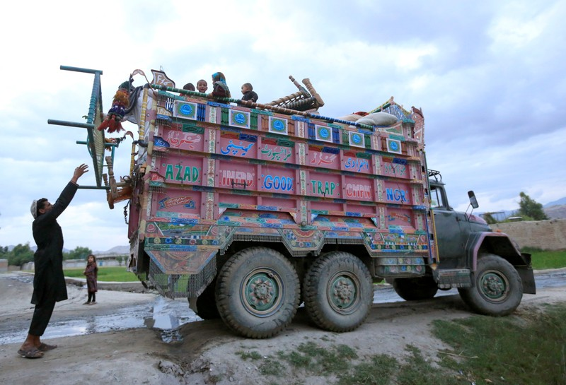 Afghan villagers who fled from the fighting sides arrive at the Behsud district of Nangarhar province