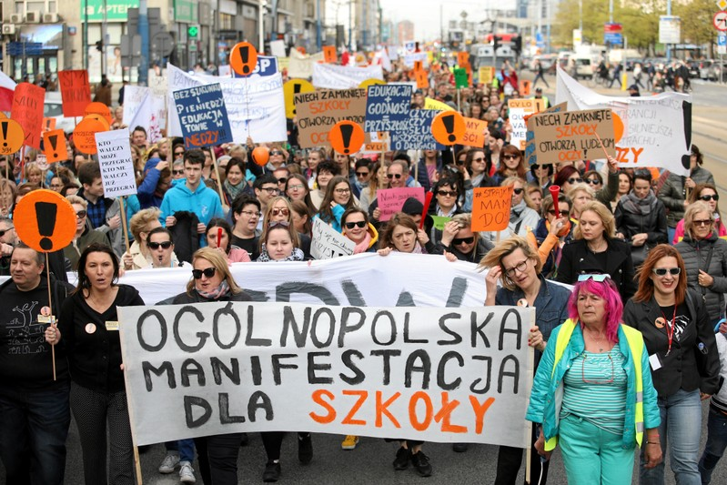 People hold banners during a rally to support a nationwide teachers' strike in central Warsaw