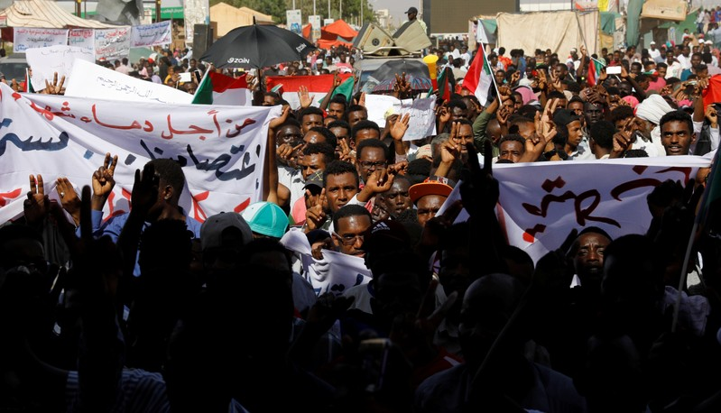 Sudanese protesters march outside the defence ministry compound in Khartoum