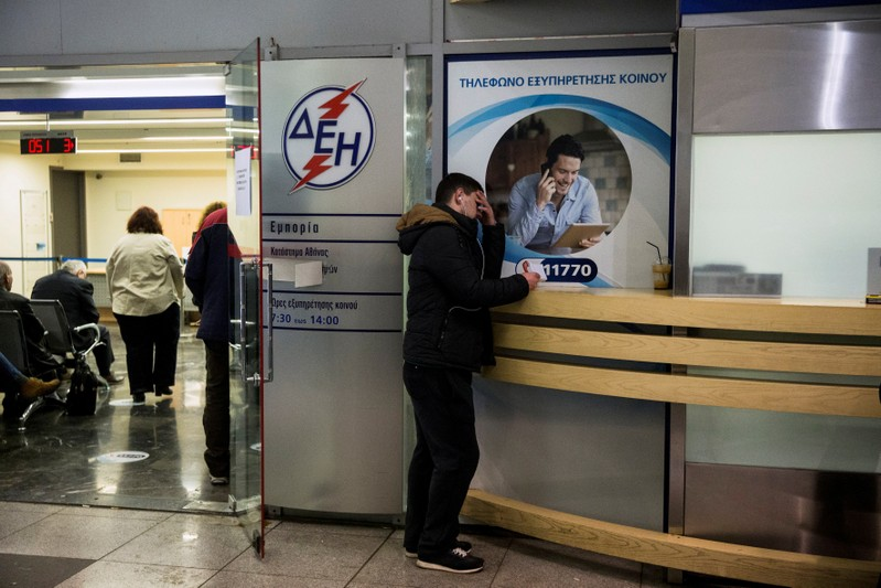 FILE PHOTO: A man waits at a Public Power Corporation (PPC) branch to enter a repayment scheme for their debts in Athens