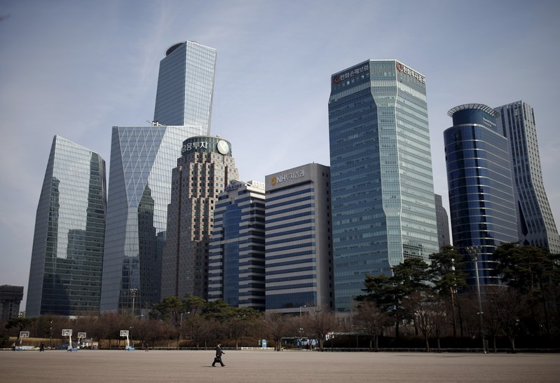 A man walks in a park at a business district in Seoul