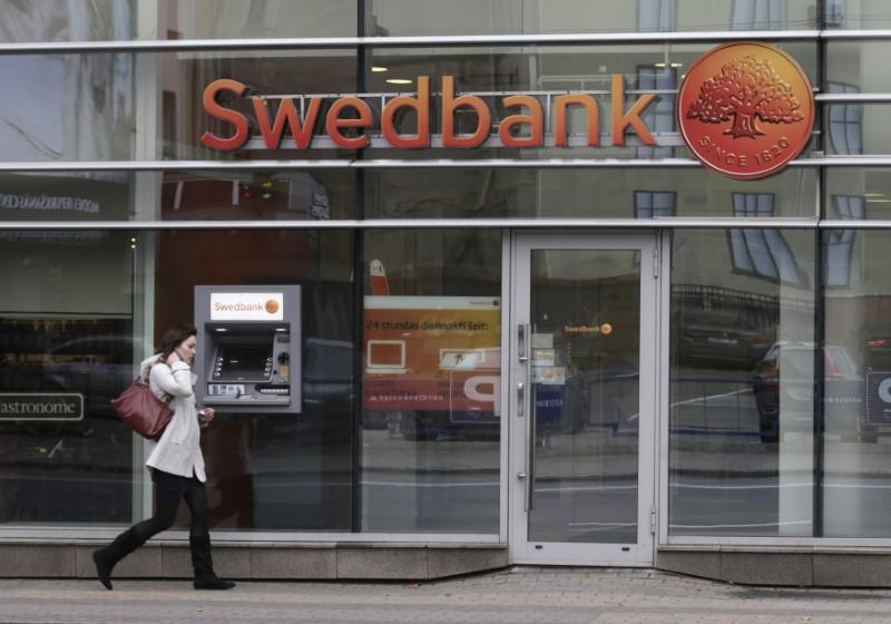 FILE PHOTO: A woman walks past Swedbank branch in Riga