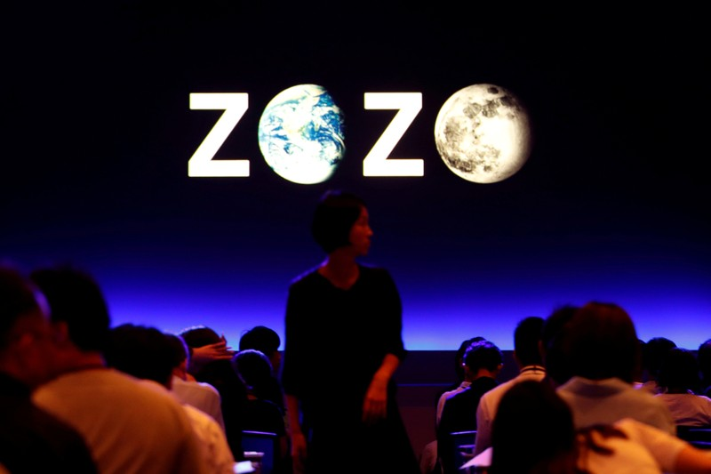 FILE PHOTO: A woman is seen in front of the logo of Zozo, which operates Japan's popular fashion shopping site Zozotown and is officially called Start Today Co, at an event launching the debut of its formal apparel items, in Tokyo