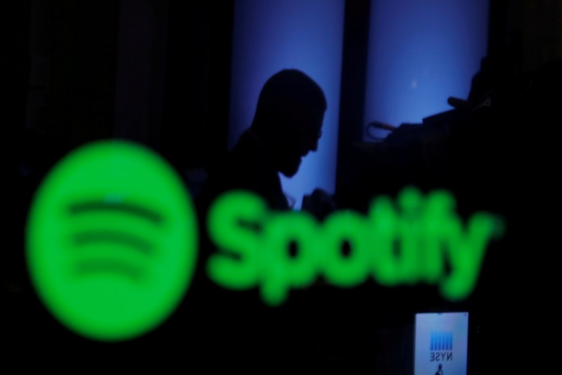 FILE PHOTO: A trader is reflected in a computer screen displaying the Spotify brand before the company begins selling as a direct listing on the floor of the New York Stock Exchange in New York