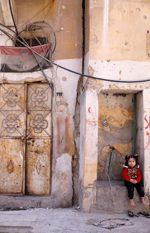 Child sits near a Syrian flag with President Bashar al-Assad at Aleppo's Kalasa district