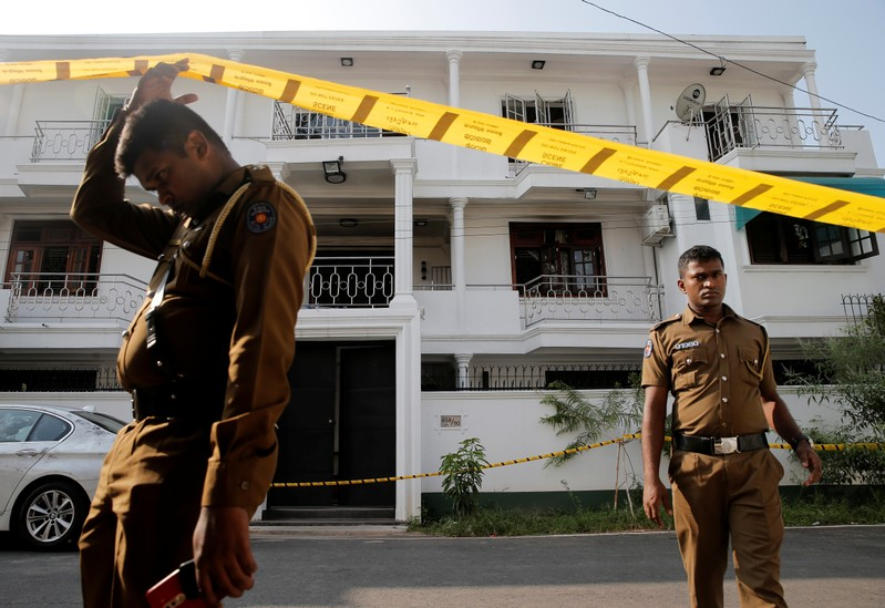 Police keep watch outside the family home of a bomber suspect where an explosion occurred during a Special Task Force raid in Colombo