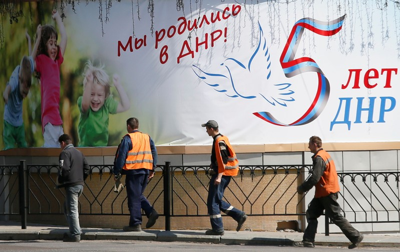 Men walk past a banner in the separatist-controlled city of Donetsk