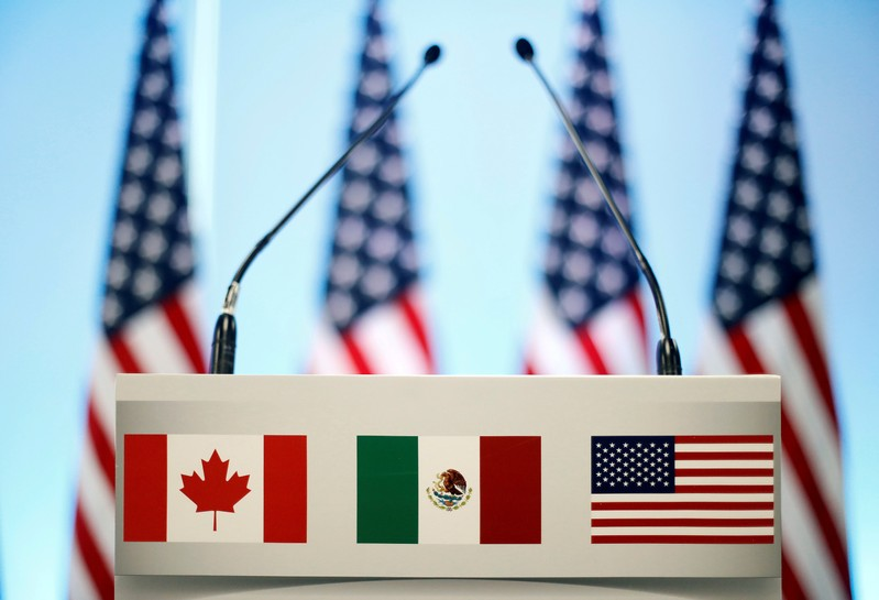 FILE PHOTO: The flags of Canada, Mexico and the U.S. are seen on a lectern before a joint news conference on the closing of the seventh round of NAFTA talks in Mexico City