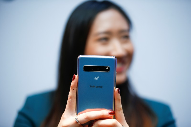 A Samsung employee poses with the new Samsung Galaxy S10 5G smartphone at a press event in London