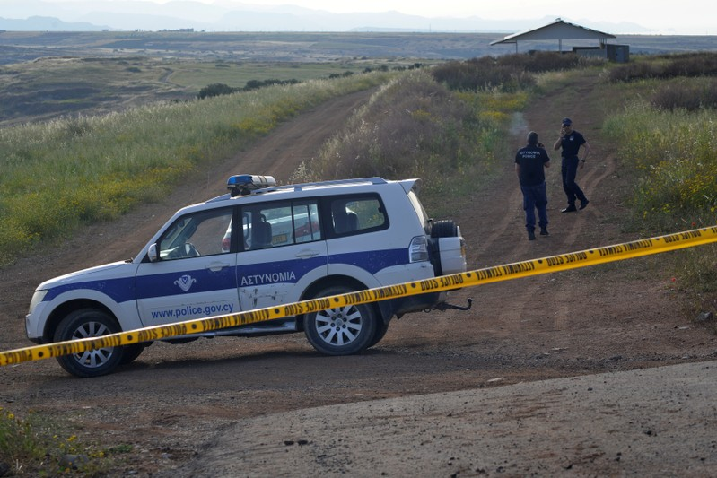 Police secure the area where the body of a woman was discovered near the village of Orounta