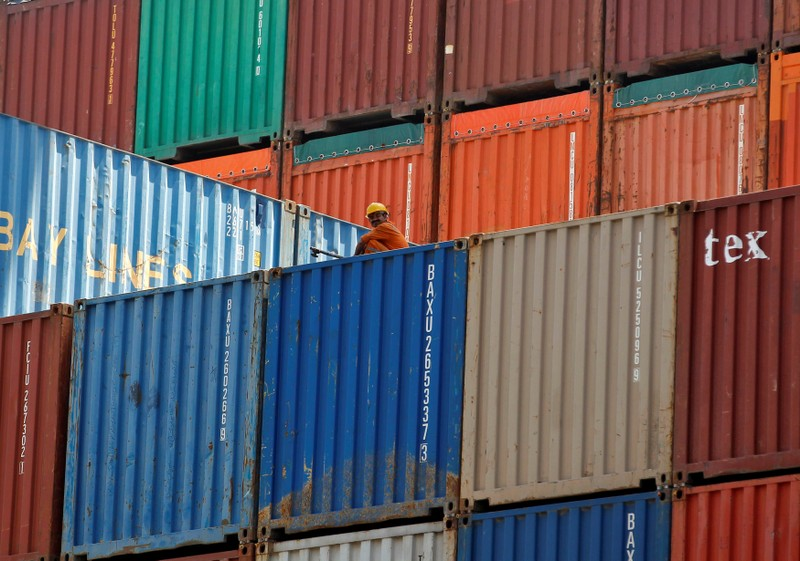 FILE PHOTO - A worker sits on a ship carrying containers at Mundra Port in the western Indian state of Gujarat