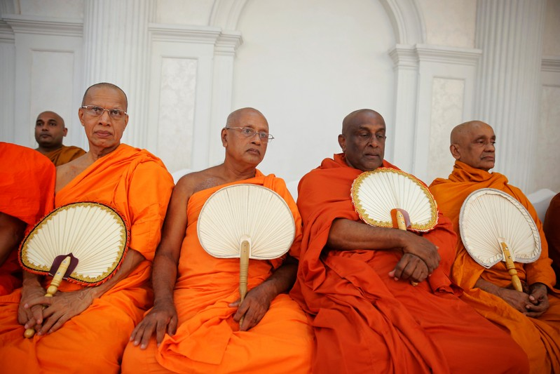 Monks take part in a Buddhist ceremony as a tribute to victims, a week after a string of suicide bomb attacks across the island on Easter Sunday, at Kingsbury Hotel in Colombo