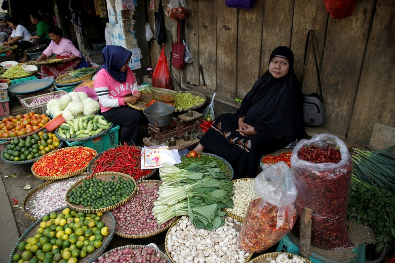 FILE PHOTO: A vegetable seller sits while waiting for customers at the morning market in Jakarta, Indonesia