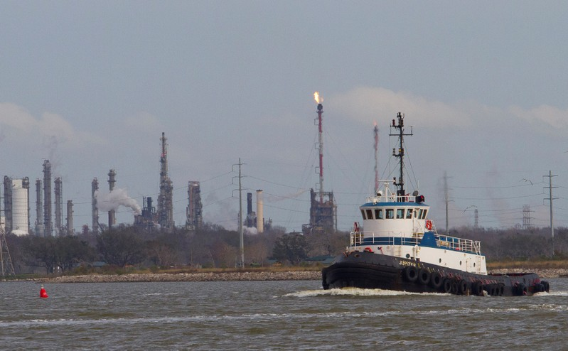 FILE PHOTO: A tug boat navigates the Houston ship channel with a flare from an oil refinery and storage facility in the background south of downtown Houston
