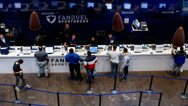 FILE PHOTO: People make their bets at the FANDUEL sportsbook during the Super Bowl LIII in East Rutherford, New Jersey
